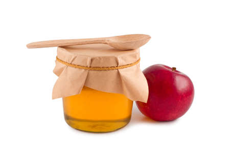 Honey in jar wooden spoon red apple isolated. Standard-Bild