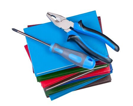 flat nose: Building tool, screwdriver and pliers on a stack of books. Objects isolated on white background
