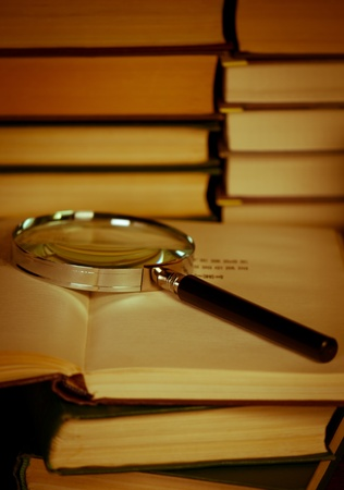 Books with magnifying glass. Concept education and science.