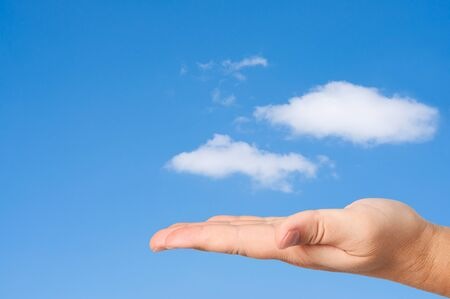 Hand in sky clouds background. Concept of environmental protection. photo