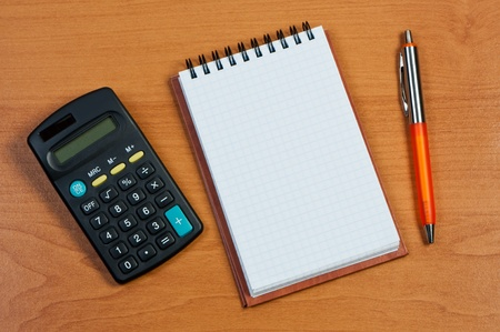 Calculator, notepad and pen on wooden background.