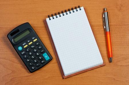 Taschenrechner, Notizblock und Stift auf Holzuntergrund. Standard-Bild - 11590964