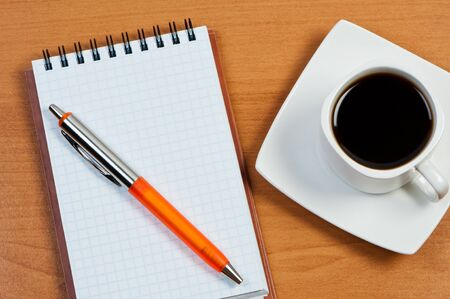 Notebook with pen and coffee on table top view.
