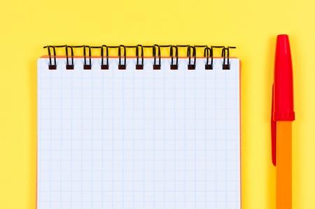 ballpen: Notepad and ballpen on yellow background. Stock Photo
