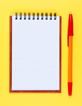 pocketbook: Pocketbook and ballpoint pen on yellow background. Stock Photo