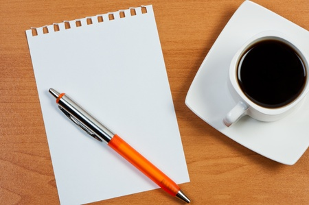 Worksheet with pen and coffee on table. photo
