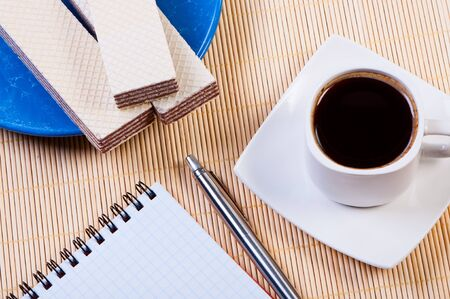 Coffee with waffles. Notepad and pen are near. photo