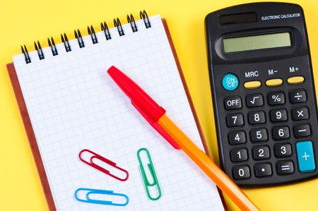 Notepad with pen and paper clips, calculator near. photo
