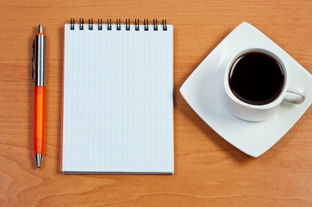 Pen, notebook and cup coffee on table. View from above. photo