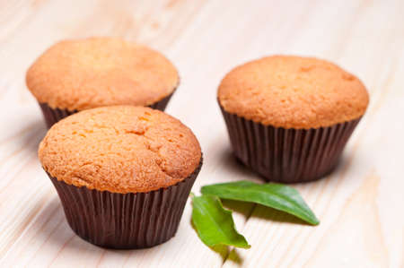 farinaceous: Cupcake in paper container on board decorated with green leaves.