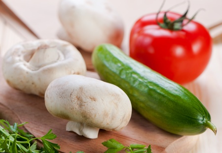 Mushrooms and vegetables on cutting board. Stock Photo - 12114788
