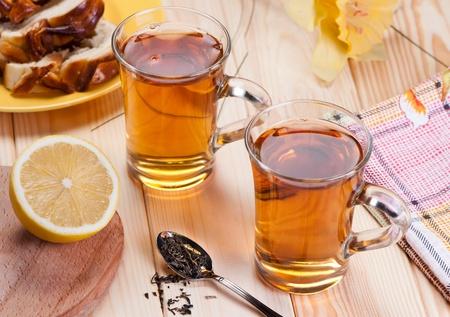 Tea with lemon on wooden table.