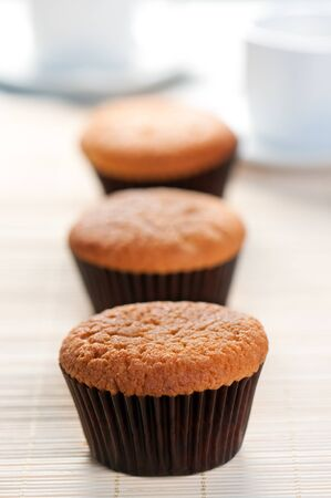 undecorated: A row of three scrumptious freshly baked undecorated golden muffins in cups with focus to the first Stock Photo
