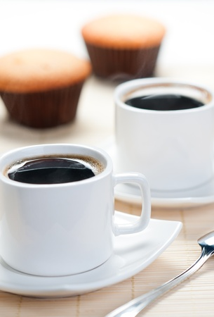 Two cup of hot coffee with muffins in the background Stock Photo - 12610759