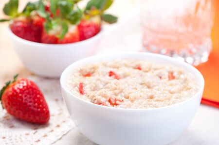 bowl of cereal: Milk porridge with slices of fresh strawberries, berries in the background