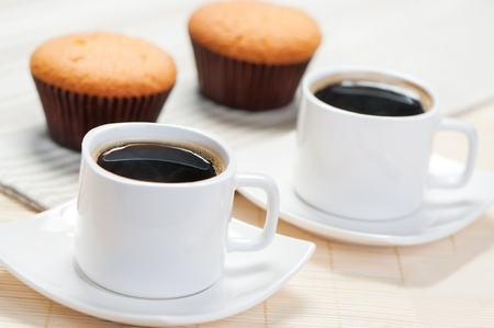 Two cups of black coffee with a delicious cupcakes in the background Stock Photo