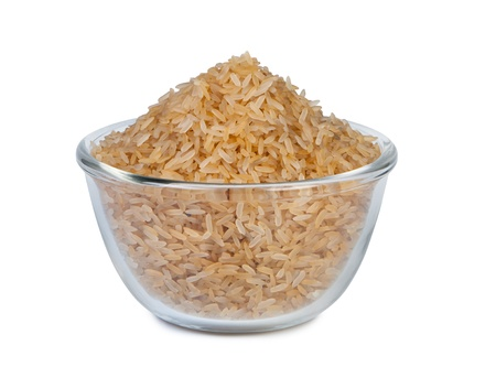 Raw brown rice in glass bowl on white background