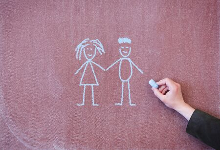 Boy and girl holding hands. Drawing with chalk on blackboard.