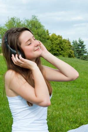 Girl in headphones listens to music in park. Stock Photo - 14244721
