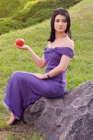 Young girl in evening dress sitting on rock and holds apple in his hand. photo