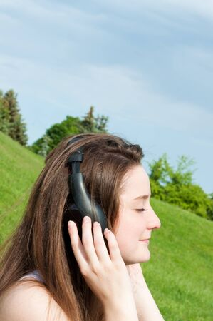 Young girl listens to music headphones summer in park. Stock Photo - 14296977