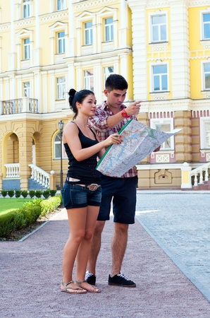 Girl and guy with map on street.