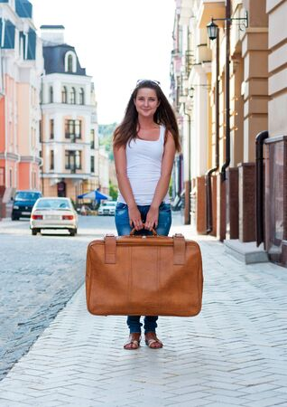 Girl on the street holding a large suitcase. photo