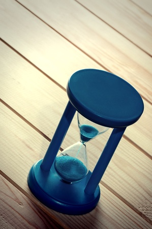 Hourglass on wooden boards. Stock Photo