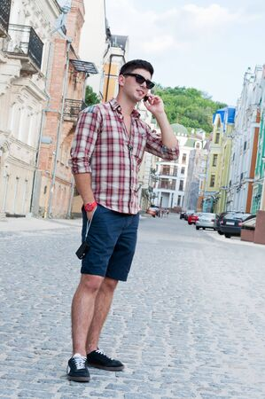 beautiful boys: Young man talking on a cell phone on the street. Stock Photo