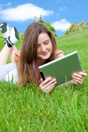 Smiling happy girl lying on grass in park with tablet. photo