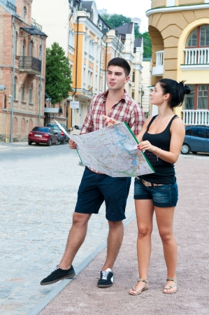 Young couple looking at a map while traveling through the city.