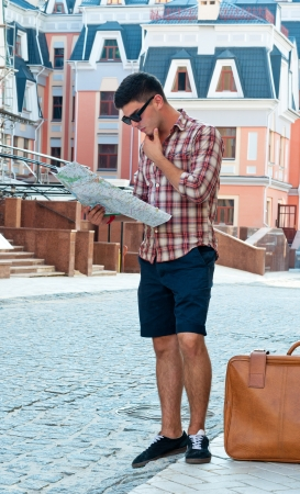 lost city: Young man with a suitcase in a thoughtful look at the map on city street. Stock Photo