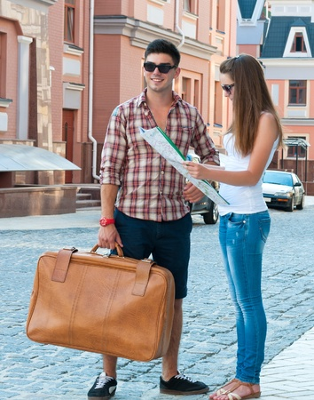 Girl with map and guy with suitcase on street. photo
