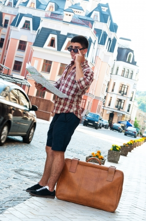 lost city: Young man with map and suitcase standing on side of street.