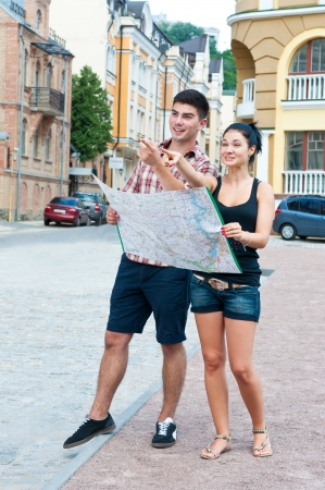 Young couple on street with a map show direction of arms. Standard-Bild