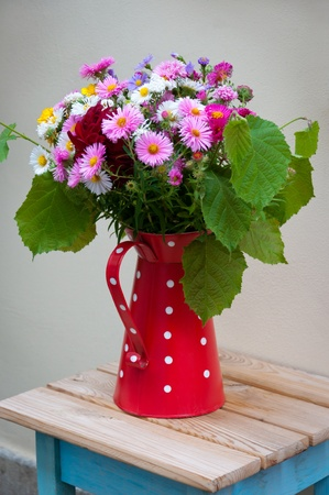 Beautiful bouquet of colorful flowers in a jug. photo
