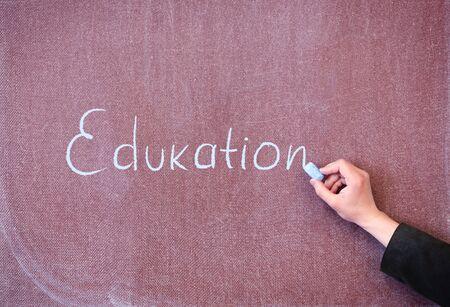 Word education written by man with chalk on blackboard. photo