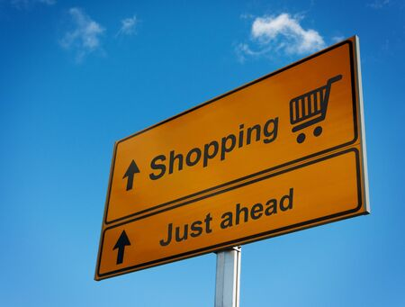 Shopping road sign with cart just ahead. photo