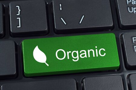 organics: Green computer keyboard button with the word organic and leaf icon. Concept of ecology and organics.