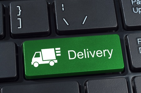Keyboard button with truck icon and text delivery Internet concept.