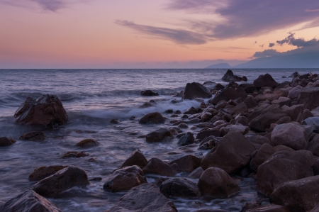 boulder: Stones on beach during a beautiful sunset over sea. Stock Photo