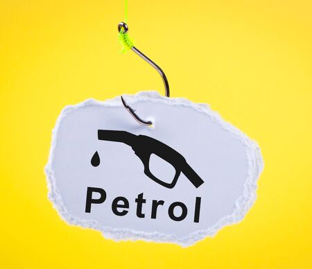 carbondioxide: Piece of paper on fishing hook with fuel nozzle. Concept using alternative fuels.