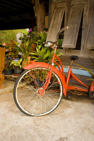 antique tricycle: Trike and old wooden houses in Thailand pathways.