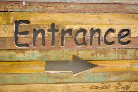 Wooden sign at the entrance to the letters and arrows. photo