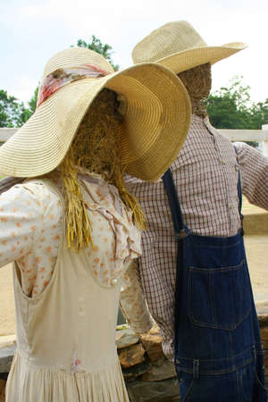 Scarecrows dressed as a farmer with spouses. photo