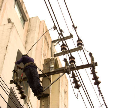 Electricians climb poles to repair the damaged equipment. photo