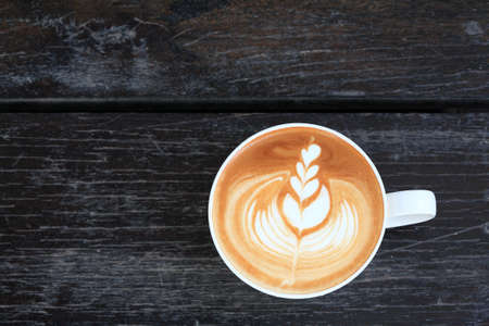 Latte art in white cup on wooden background photo