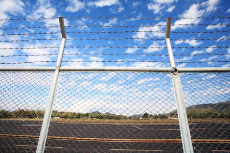 Barbed wire fence against blue sky  photo