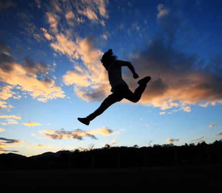 man jumping againts dark blue sky background   photo