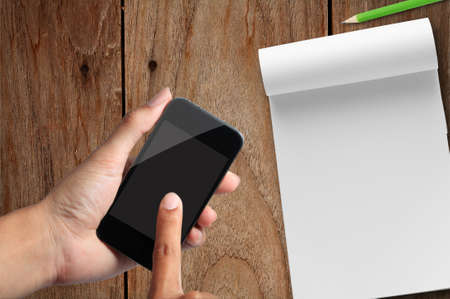 hand pressing smart phone in workspace Stock Photo - 13267465